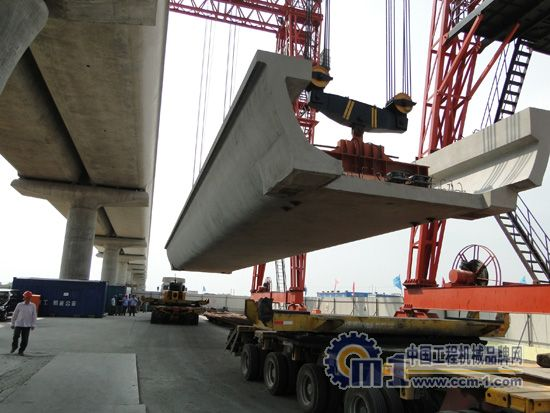 据项目部总工吴昊介绍,上海机施公司承建的标段共有7.66公里,范围内均为高架桥,主要结构形式为下部为独立隐形盖梁式桥墩,上部为预制简支U型梁,U型梁数量共462榀。沿线基本为未建成的临港大道,目前都是农田、苗圃及河浜,水系发达。U形梁架设跨跃多条主干道路及有通航要求的河流,施工现场条件较差、各方干扰较大。   上海机施公司根据架梁施工条件状况,选用了温州合力建机的4台提梁机(也叫龙门吊,22m和40m跨度各2台)、2台运梁车和一台220t架桥机等成套设备来架设U型梁。线路的架梁施工方法为定点上梁,