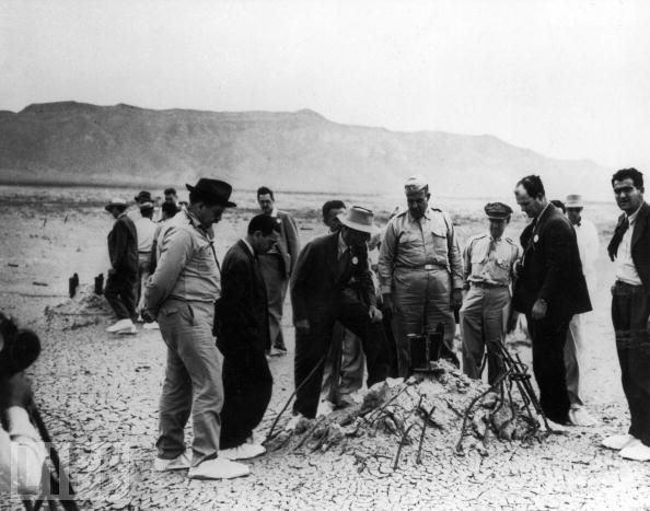 """""""曼哈顿计划""""的领导人包括奥本海默(图中头带白帽者)以及军方负责人格罗夫斯将军(图中正中间身穿军服者)。1945年7月16日,美国成功在新墨西哥州的阿拉莫戈多试爆世界上第一颗核弹。图为相关负责人在爆炸试验后查看现场时的情景。"""