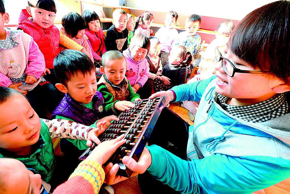12月5日,省公路局幼儿园,老师正给孩子们讲述算盘的来历。珠算作为我国古老的一种进行数字计算的工具,被誉为中国的第五大发明,12月4日又被联合国教科文组织列入人类非物质文化遗产名录。省城各小学、幼儿园近年来注重传统文化教育,非物质文化遗产引起了孩子们的浓厚兴趣。
