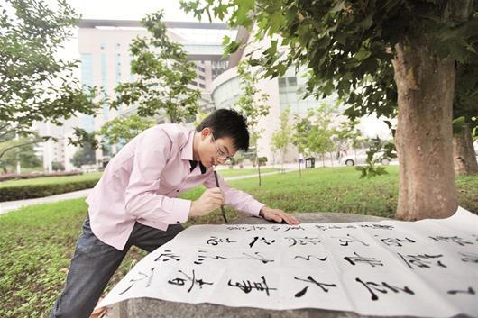 楚天都市报讯 图为:吴良博常在校园里创作书法作品
